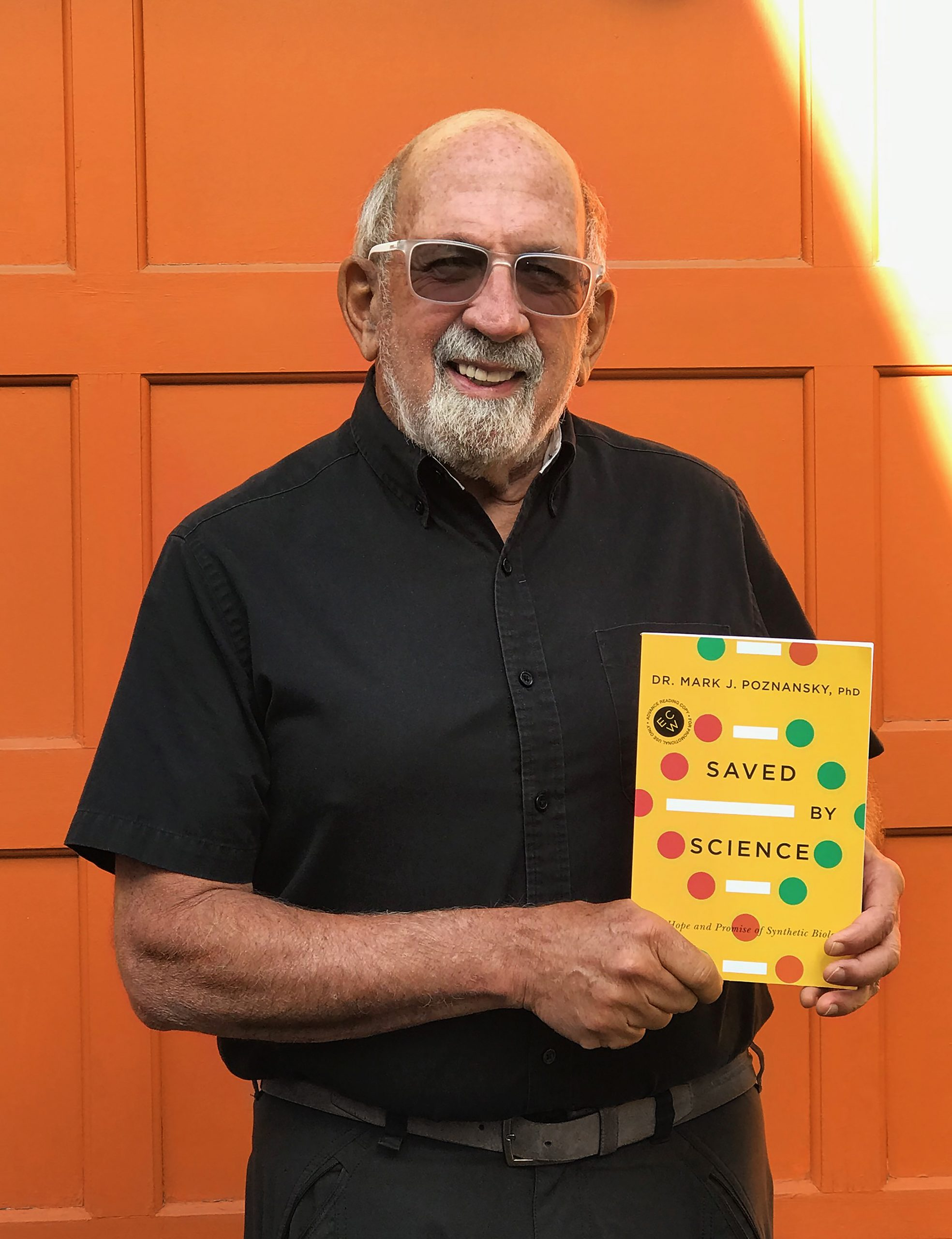 """Image of Mark Poznansky standing with his book, """"Saved by Science"""""""